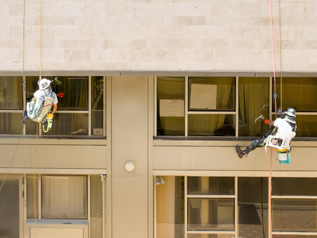 Two professional workers washing windows on a building