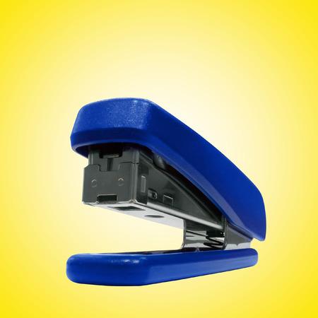 office stapler: Blue office stapler isolated over yellow background