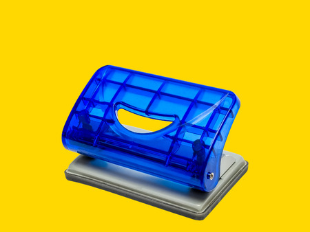 puncher: Blue office hole puncher against yellow background