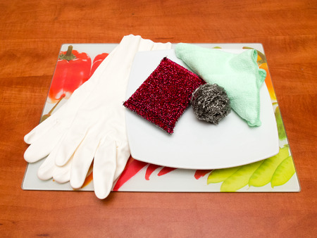 dish washing gloves: Dish washing sponge, dishcloth, rubber gloves, scrub pad, plate and colored tray on a table.