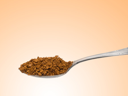teaspoon: Old silver teaspoon with granulated instant coffee isolated on brown