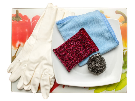 dish washing gloves: Dish washing sponge, dishcloth, rubber gloves, scrub pad and plate on colored tray. Top view.