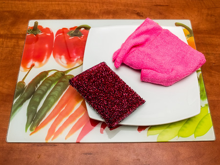 dishcloth: Dishcloth, scrub pad, plate and colored tray on a table. Stock Photo