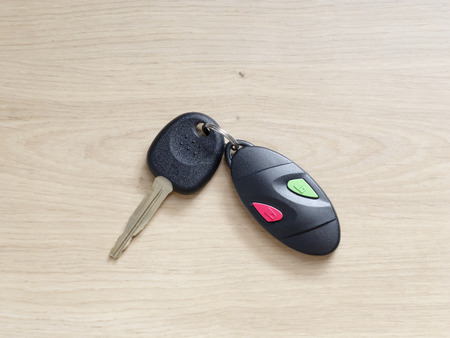 car accessory: Car key with remote control on a wooden background