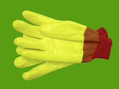 class maintenance: Pair yellow protective working gloves against green background.