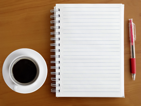 papel de notas: Directly above view of notebook, pen and cup of coffee on wooden table