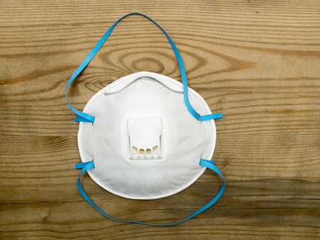 protects: Industrial respirator with valve protects against dust over wooden background Stock Photo