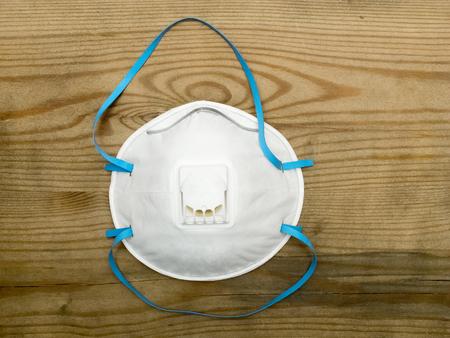 elementos de protecci�n personal: respirador industrial con v�lvula protege contra el polvo sobre fondo de madera