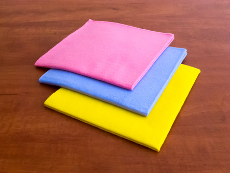 Consumables: Colorful household cleaning wipes on the wooden surface of the table Stock Photo