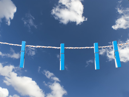 clench: Plastic clothes pegs on rope against blue sky Stock Photo