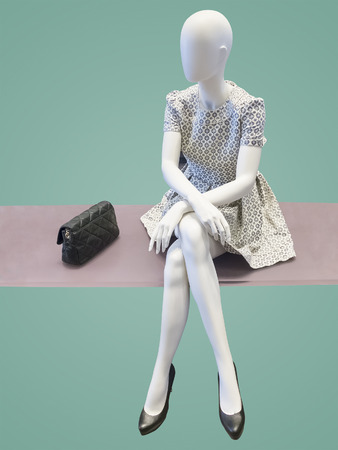 Sitting female mannequin, against green background. No brand names or copyright objects.
