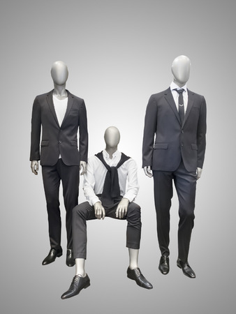 Three male mannequins dressed in suit over grey background.