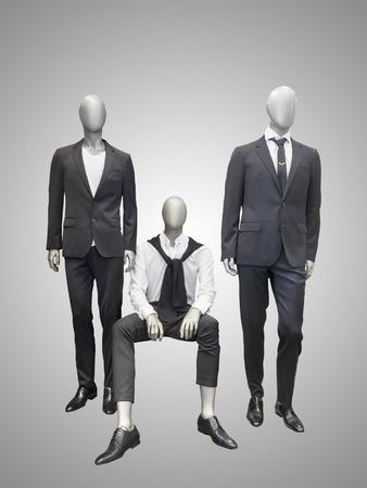 Trois mannequins hommes habillés en costume sur fond gris.