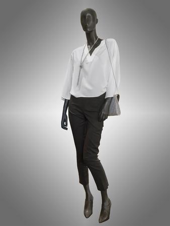 mannequin: pleine longueur mannequin femme vêtue d'une blouse blanche et un pantalon noir avec le sac