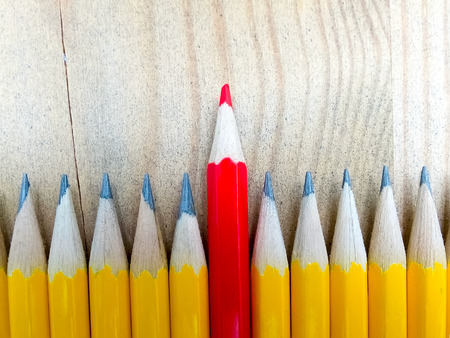 Row of black pencils with one red pencil in middle against wooden background. Out from the crowd.