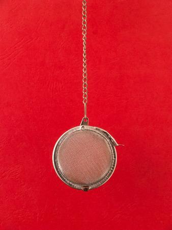 infuser: Hanging tea strainer infuser against red background