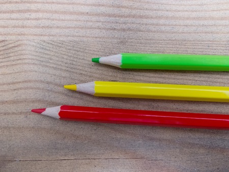 grouped: Three colored pencils grouped on wooden background