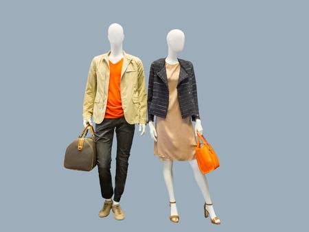 Twee mannequins, man en vrouw, gekleed in vrijetijdskleding. Geïsoleerd op grijze achtergrond