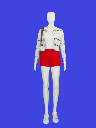 red shorts: Full-length female mannequin dressed in red shorts and white jacket on blue background Stock Photo