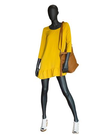 Pleine longueur mannequin femme habillée en robe jaune isolé sur fond blanc.