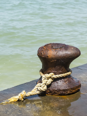 tied knot: Old iron rusty mooring bollard at a harbor with tied knot
