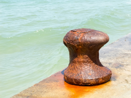 mooring bollard: Old iron rusty mooring bollard at a harbor Stock Photo