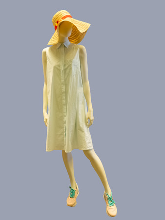 Female mannequin wearing summer dress and straw hat, against grey background. No brand names or copyright objects.
