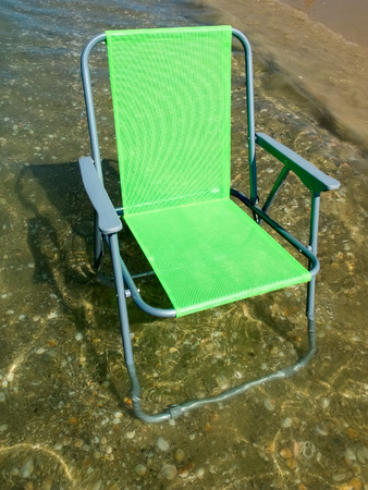 collapsible: Green folding camp chair standing in water near the beach Stock Photo