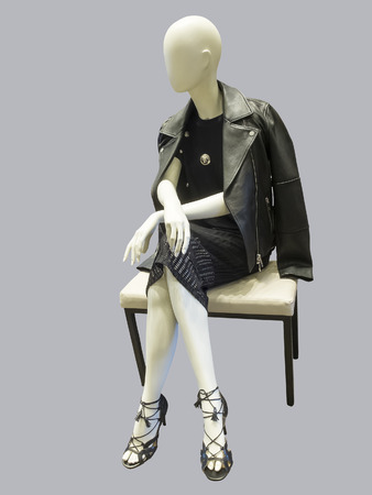 Sitting female mannequin wearing black dress and leather jacket, against grey background.  No brand names or copyright objects. Stock Photo