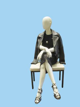 Sitting female mannequin wearing black dress and leather jacket, against blue background.  No brand names or copyright objects.