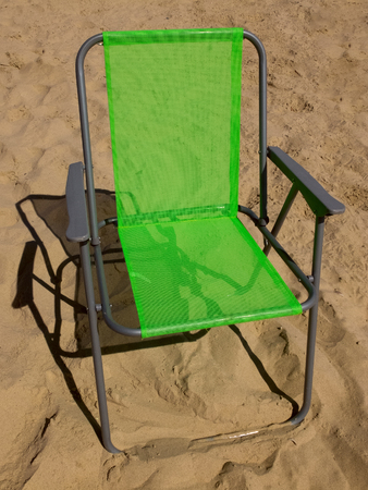 seclusion: Green folding camp chair standing on a sand