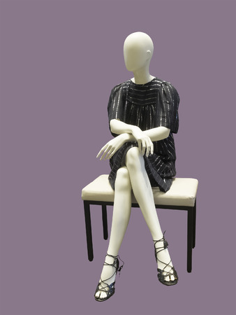 Sitting female mannequin wearing black dress, against lilac background.  No brand names or copyright objects.