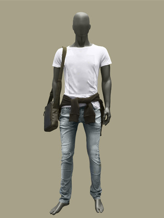 Full length male mannequin dressed in shirt and blue jeans, isolated on brown background. No brand names or copyright objects. Stock Photo