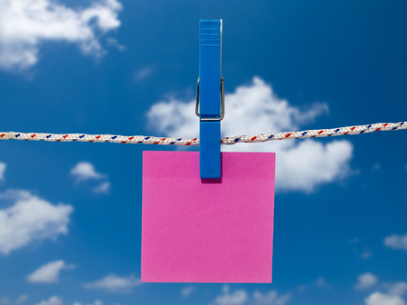 Single blank square of red paper suspended from a washing line by plastic peg against blue sky.