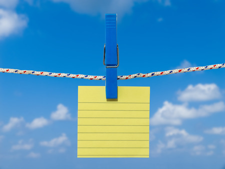 Single blank square of yellow paper suspended from a washing line by plastic peg against blue sky.