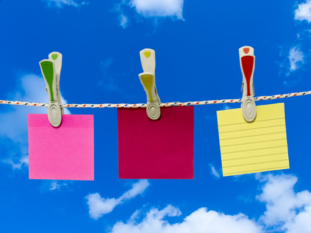 Three blank square of paper suspended from a washing line by plastic pegs against blue sky. Stock Photo