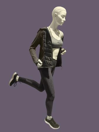 busty: Corriendo maniquí femenino aislado en fondo lila. No hay nombres de marca ni objetos de derechos de autor.