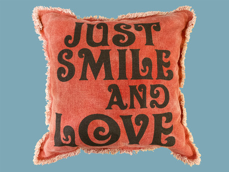 tender sentiment: Red couch cushion with JUST SMILE AND LOVE text written on it,  isolated on blue background.