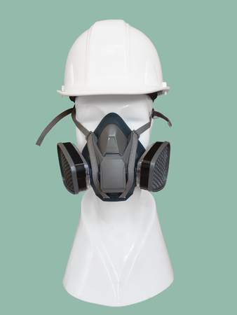 Dust mask with valve and safety helmet on mannequin, isolated on green background. Stock Photo