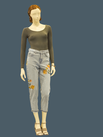 Full-length female mannequin dressed in jumper and blue jeans, isolated. No brand names or copyright objects. Stock Photo