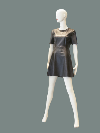Full length female mannequin wearing gray dress, against green background. No brand names or copyright objects.