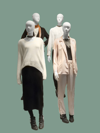 four objects: Four female mannequins dressed with fashionable modern clothes, isolated on green background. No brand names or copyright objects. Stock Photo