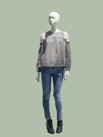 Full-length female mannequin wearing blouse and blue jeans, isolated. No brand names or copyright objects.
