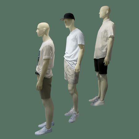 Three man mannequins dressed in summer casual clothes over green background. No brand names or copyright objects.