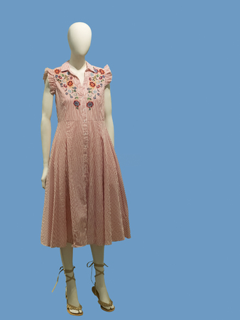 Full-length female mannequin in stripped pink dress isolated on blue background.