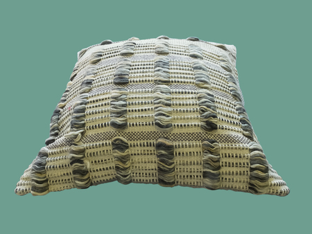 Decorative cushion with knitted pattern over green background.