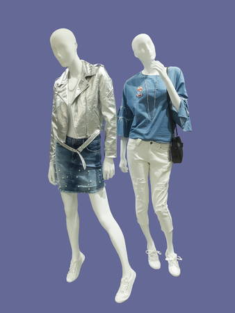 Two full-length female mannequins dressed in fashionable clothes, isolated. No brand names or copyright objects.