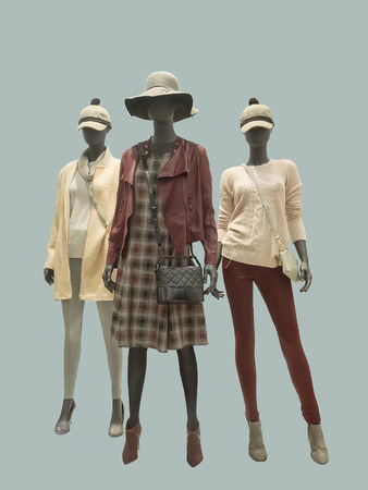 Three female mannequins dressed in fashionable clothes, isolated. No brand names or copyright objects.