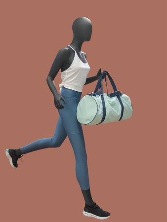 Running female mannequin with duffel bag, isolated. No brand names or copyright objects.