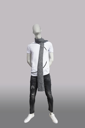 Full-length male mannequin dressed in t- shirt and black ripped jeans, isolated. No brand names or copyright objects.
